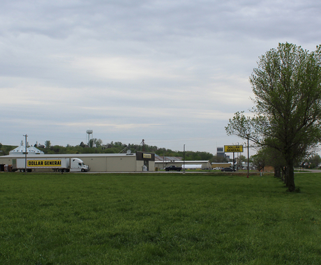 Dollar General building with Dollar General Truck in front at edge of town