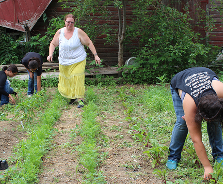 Family pulling weeds in front of barn