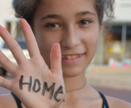 "Girl with ""home"" written on her hand"