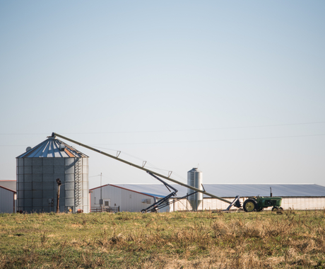 tractor unloading crop at grain bin