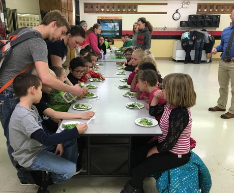 Children sitting at lunch table eating salad