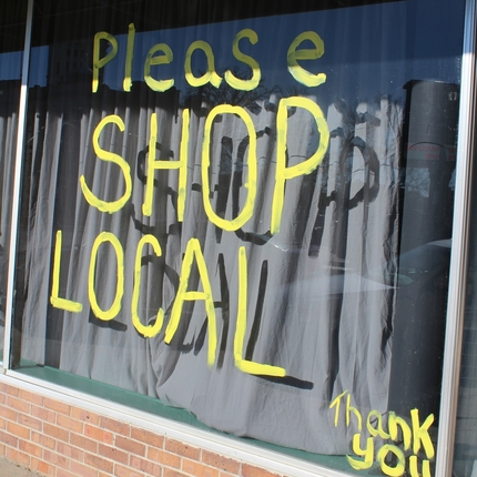 Storefront with painted 'please shop local'